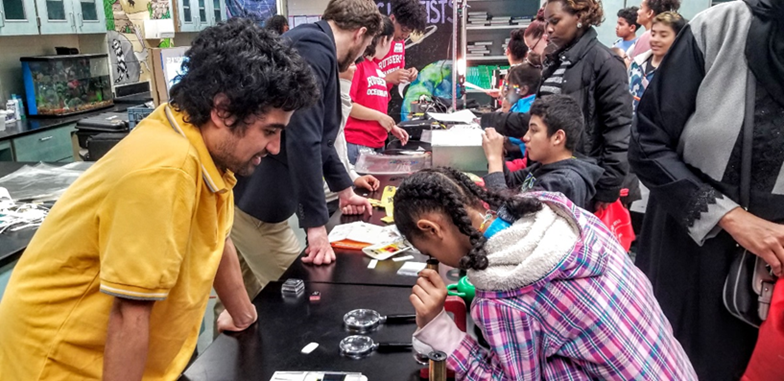 Dr. Saroj Poudel exploring our microscopic world with students who constructed their own paper foldscopes.